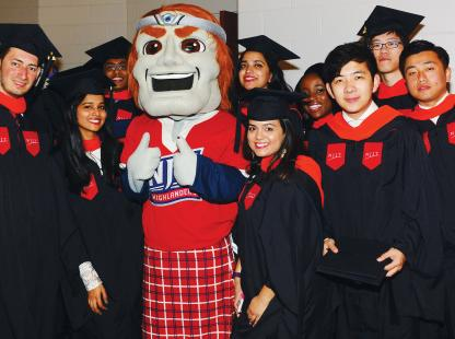 Photo of the NJIT mascot and students at a commencement ceremony